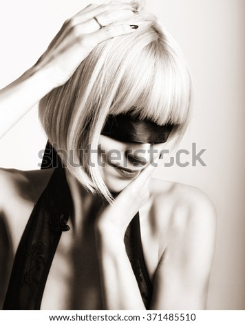 Close up portrait of beautiful sexy young blonde woman  with a bandage on his eyes, puts her hand to her hair. black and white - stock photo