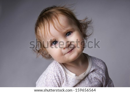 Close-up portrait of beautiful smiling baby girl, studio shot