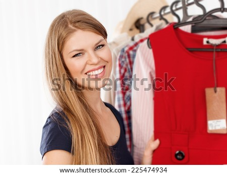 Close up portrait of beautiful smiling female retail shop owner standing at clothing rack. Young woman clothes store proprietor adjusting dresses.  - stock photo
