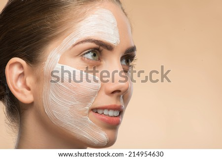 Close-up Portrait of beautiful smiling girl in spa with cosmetic cream on her face with clean and  fresh skin looking aside isolated on beige background  with copy place - stock photo