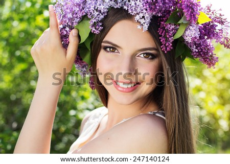Close up portrait of beautiful smiling girl with fashion makeup is wearing beautiful wreath of lilac flowers - stock photo
