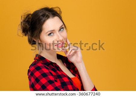 Close up portrait of beautiful smiling young woman in checkered shirt isolated over yellow background - stock photo