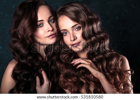 close-up portrait of beautiful twins young women with natural make-up and hair style. fashion beauty photo