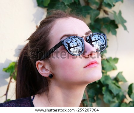 Close-up portrait of beautiful woman in black sunglasses on gray background  - stock photo