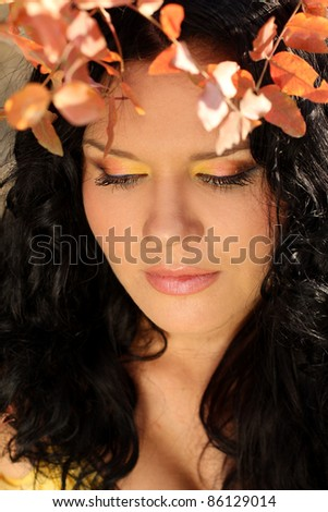 Close-up portrait of beautiful woman in red autumn leaves - stock photo