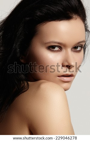 Close-up portrait of beautiful woman's purity face with fashion dark smoky-eyes make-up, pale lips. Sexy model with clean shiny skin, purity complexion and volume brunette hairstyle. Long curly hair  - stock photo