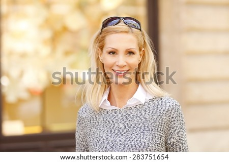 Close-up portrait of beautiful woman standing on the street while looking at camera and smiling. - stock photo