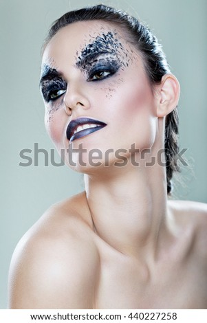 close up portrait of beautiful woman with artistic make up isolated on neutral background in photo studio