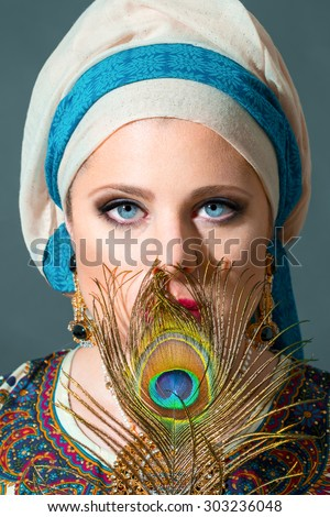 Close up portrait of beautiful  woman  with blue eyes wearing turban and holding peacock feather - stock photo