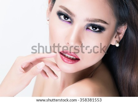 Close-up portrait of beautiful woman with bright make-up and red lips