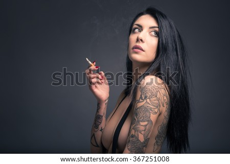 Close up portrait of beautiful woman with tattoo smoking, wearing short jeans paint against dark background. - stock photo