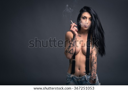 Close up portrait of beautiful woman with tattoo smoking, wearing short jeans paint against dark background.