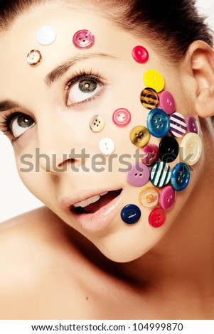 Close up portrait of beautiful woman with various colorful buttons on her face