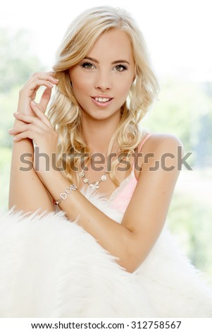 Close up portrait of beautiful young adult attractive sexy and sensuality pretty blonde woman wrapped in white fur