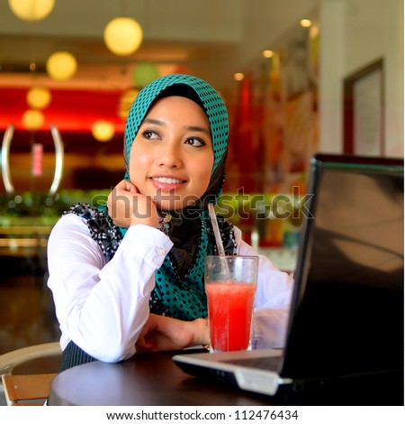 Close-up portrait of beautiful young Asian Muslim woman at cafe - stock photo