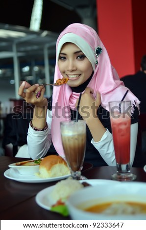 Close-up portrait of beautiful young Asian Muslim woman at cafe