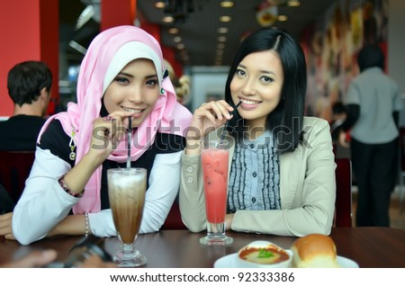 Close-up portrait of beautiful young Asian Muslim woman at cafe with lovely smiles