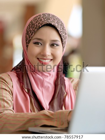 Close-up portrait of beautiful young Asian Muslim woman at coffee shop with lovely smiles - stock photo