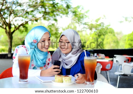 Close-up portrait of beautiful young Asian student study and drink together - stock photo