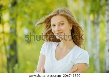 close-up portrait of beautiful young blond woman in white blouse at park holding her neck - stock photo