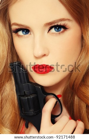Close-up portrait of beautiful young blond woman with revolver in hand - stock photo