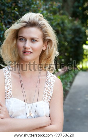 close-up portrait of beautiful young blonde woman in white blouse at park holding her neck
