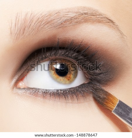 close up portrait of beautiful young brunette woman applying eye-zone make up with cosmetic brush