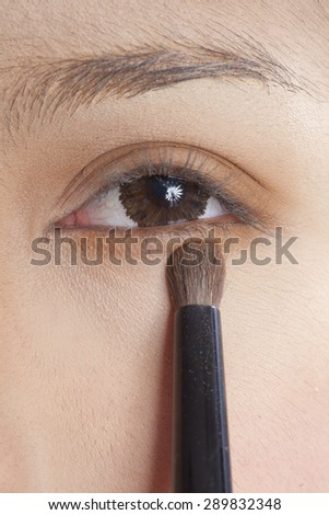 close up portrait of beautiful young brunette woman applying eye-zone make up with cosmetic brush - stock photo