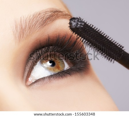 close up portrait of beautiful young brunette woman applying mascara for lash extension - stock photo