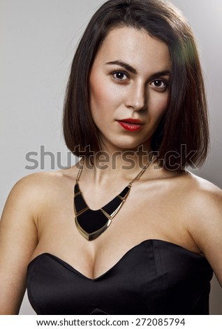 Close-up portrait of beautiful young business woman wearing black cocktail dress and nice necklace posing in front of camera. Professional make-up and hair style makes her look just stunning. - stock photo
