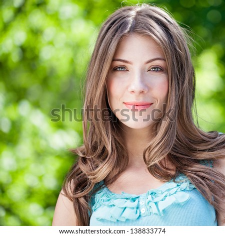 Close-up portrait of beautiful young Caucasian woman outdoors. Looking at camera. - stock photo