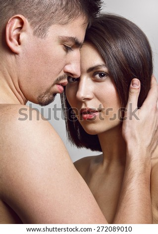 Close-up portrait of beautiful young couple posing together. She is flirting with the camera and he is touching gently her brown hair and looking at her.  - stock photo