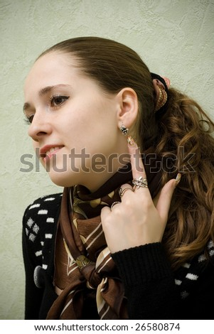 close-up portrait of beautiful young girl pointing at ear-ring