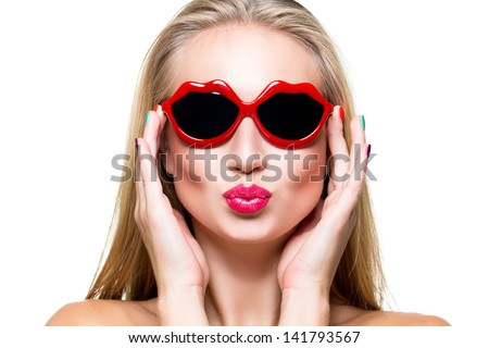 Close-up portrait of beautiful young girl with red lips wearing lips-shaped sunglasses