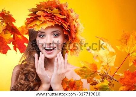 Close-up portrait of beautiful young  girlin in a chaplet from varicoloured autumn leaves on a yellow background - stock photo