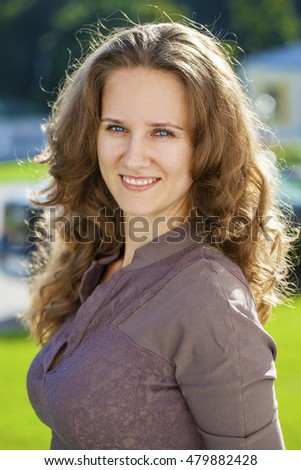 Close up portrait of beautiful young happy brunette woman in brown dress, summer park outdoors