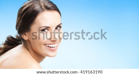 Close up portrait of beautiful young happy smiling woman, over blue background, with copyspace for slogan or text message