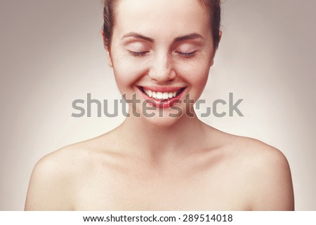 Close up portrait of beautiful young happy smiling woman wiht closed eyes, isolated over light grey background - stock photo