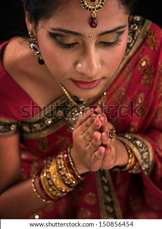 Close up portrait of beautiful young Indian woman prayer in traditional sari dress, isolated on black background.