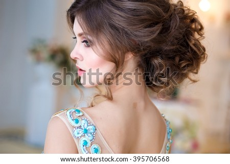 Close-up portrait of beautiful young lady in a luxury blue dress with perfect makeup and hair style - stock photo