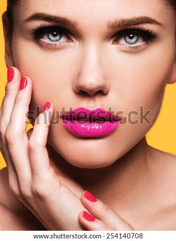 Close up portrait of Beautiful young model with pink lips and manicure, fashion look, perfect light skin, sunburn, blue eyes,isolated on yellow background - stock photo
