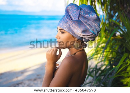 close-up portrait of  beautiful young sensual sexy woman with turban on  head and African ornaments  full lips,  expressive eyes on a sunny day at sunset in the tropical hot sand beach  sea Thailand