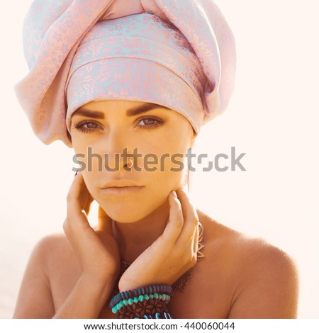 close-up portrait of beautiful young sensual sexy woman with turban on head and African ornaments full lips, expressive eyes on a sunny day at sunset in the tropical hot sand beach sea Thailand - stock photo