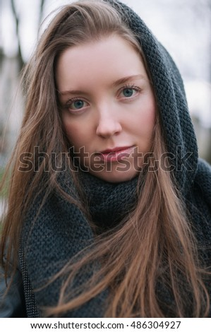 Close up portrait of beautiful young stylish girl with ideal skin in a black shawl on her head.