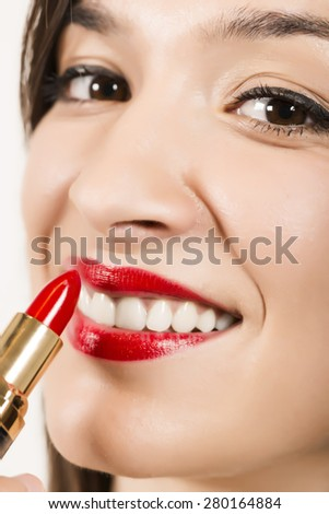 Close up portrait of beautiful young woman applying red lipstick