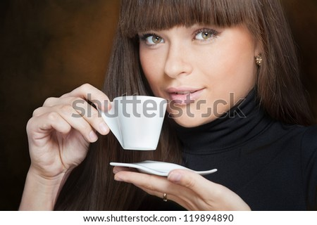 Close-up portrait of beautiful young woman drinking coffee - stock photo