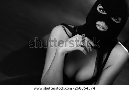 close up portrait of beautiful young woman in black sexy underwear, balaclava, lying on bed xxx - stock photo