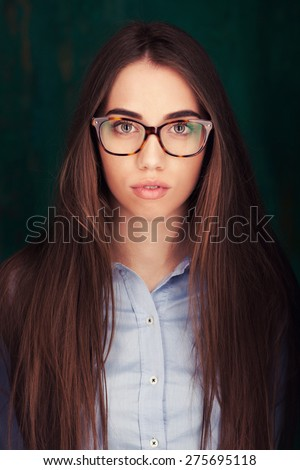 Close-up portrait of beautiful young woman in glasses on dark green background - stock photo