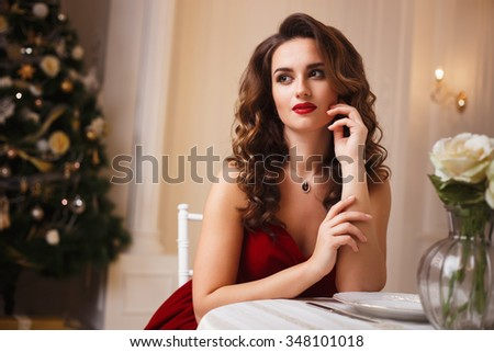 Close-up portrait of beautiful young woman in gorgeous red velvet evening dress sitting by the table in expensive interior - stock photo