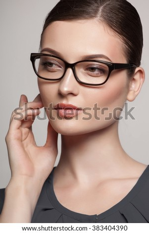 Close-up portrait of beautiful young woman in stylish glasses